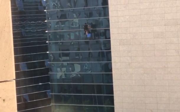 Canlı yayında binanın dışındaki camları silen kişinin yürekleri hoplatan hareketleri